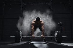 Athlete preparing to lift heavy barbell in a cloud of dust at the gym