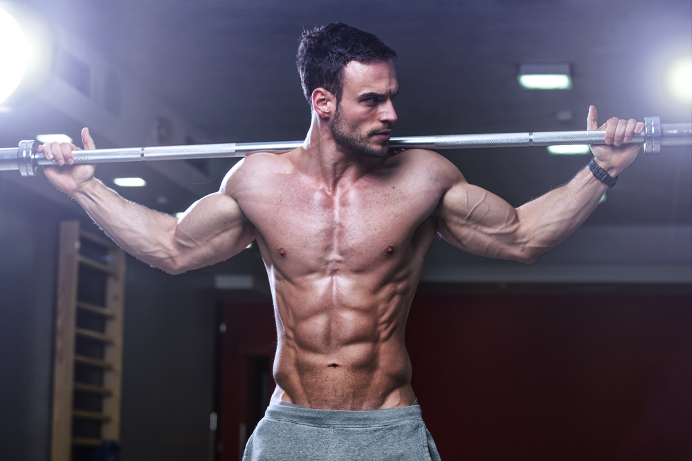 Bodybuilder holding a weight bar on his shoulders