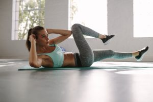 Fit young woman doing bicycle crunch workout to improve her abs