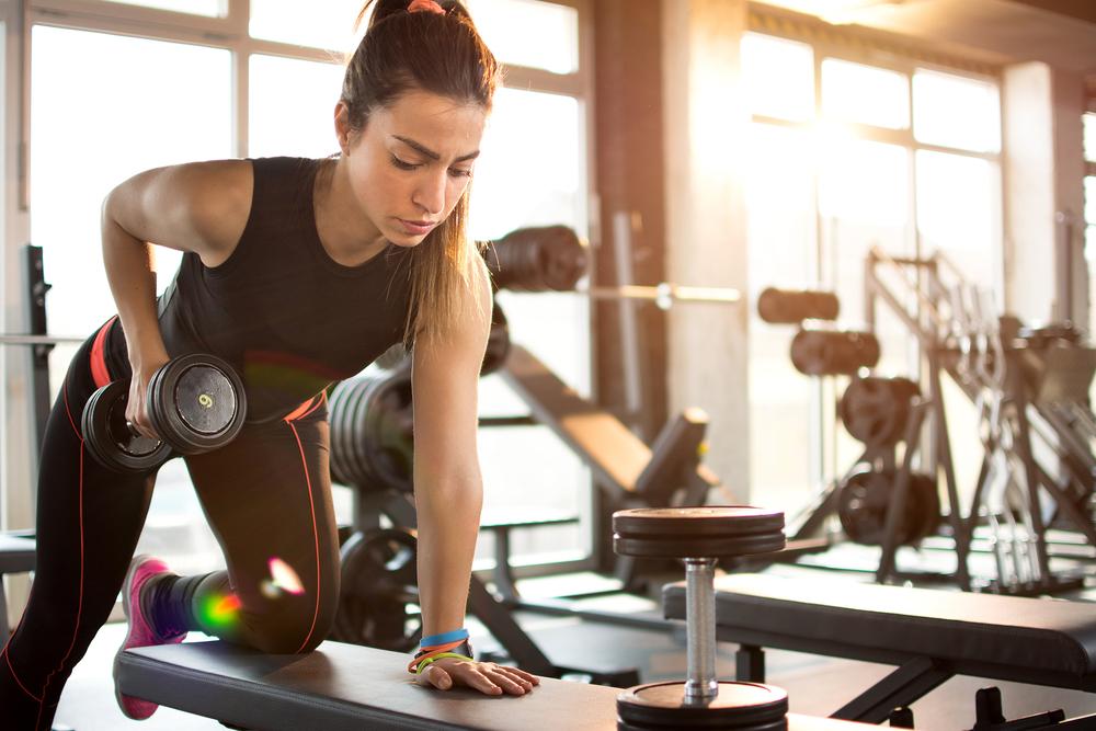 Fitness girl lifting dumbbell in the morning