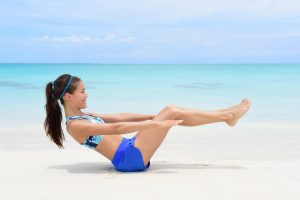 Fitness woman on beach with toned in shape body body doing v-up crunch ab toning exercise workout as part of an active lifestyle for weight loss
