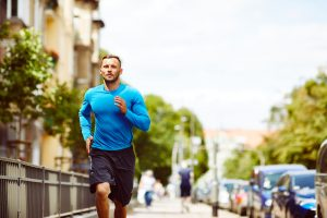 Front view of an athletic man jogging beside a busy city street
