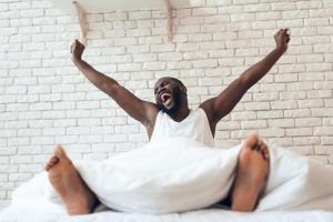 Happy awakened man is stretched out in bed