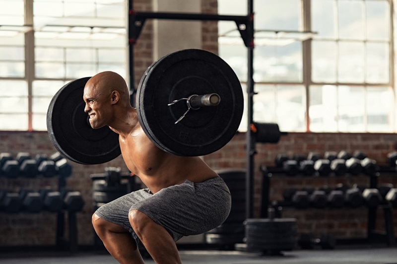 Muscular strong man taking efforts to lift weight barbell in fitness center
