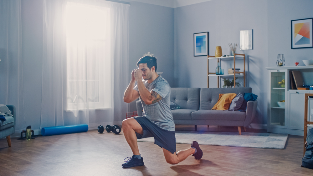 Strong Athletic Fit Man in T-shirt and Shorts is Doing Forward Lunge Exercises at Home