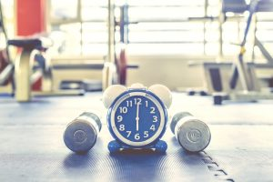 Time for exercising alarm clock and dumbbell the Gym background