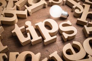 Tips wood word in scattered wood letters with glowing light bulb