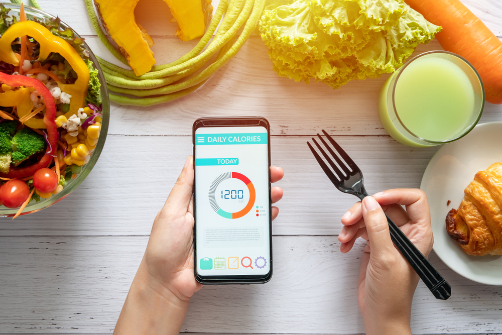 Woman using Calorie counter application on her smartphone at dining table with salad, fruit juice, bread and vegetable