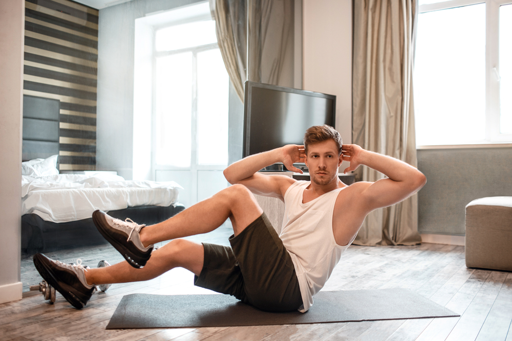Young man working out in a hotel room