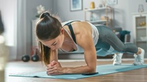Strong Beautiful Fitness Girl in Athletic Workout Clothes is Doing a Plank Exercise While Using a Stopwatch on Her Phone